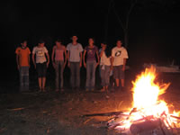 Teenagers from the Eco Club singing by the campfire