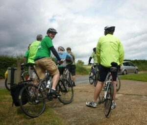 Photograph of cyclists, storm clouds looming