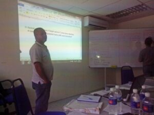 Berjaya in a classroom in front of a screen on to which information is projected.
