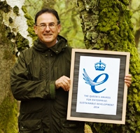 Nick Brown holds up a certificate of the Queens Award