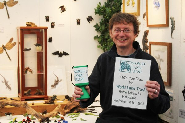 John Noble-Milner holds up a WLT collection box and raffle poster.
