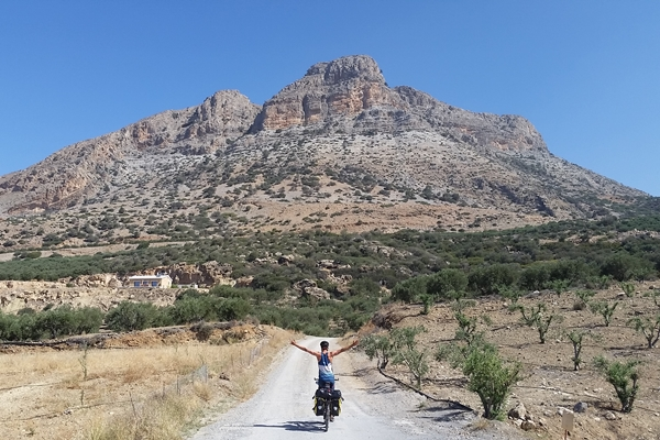 No hands! Cyclist on the road in Crete, mountain in background